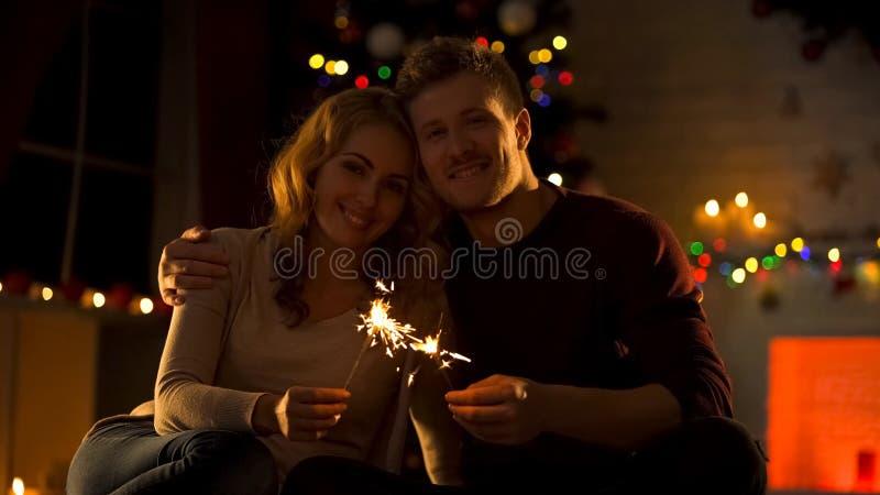 Coppie dolci con le luci di Bengala che si siedono nella stanza accogliente vicino all'albero decorato di natale fotografia stock libera da diritti