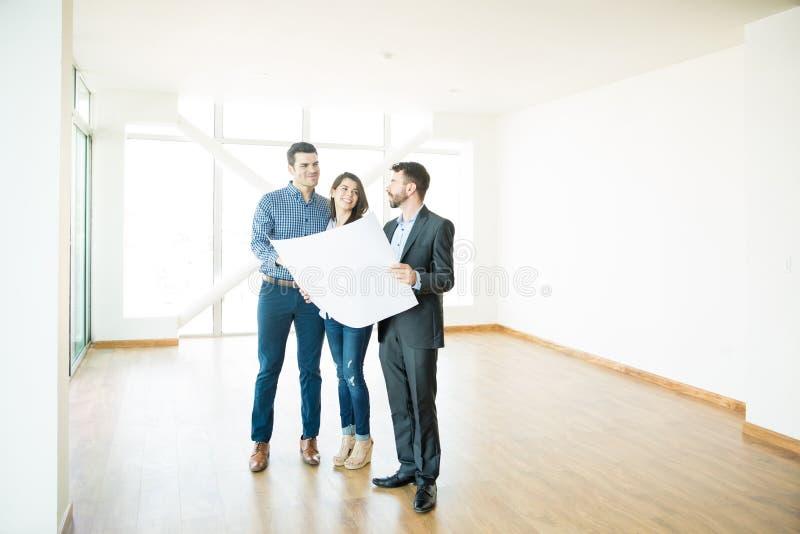 Coppie e agente immobiliare Discussing Over Blueprint in nuovo Apartme fotografie stock libere da diritti