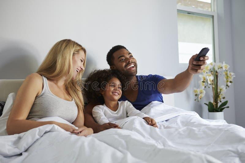 Coppie e figlia della corsa mista che guardano TV a letto insieme fotografie stock