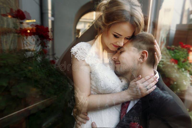 Coppie eleganti di nozze che abbracciano delicatamente in vie della città alla sera fotografia stock