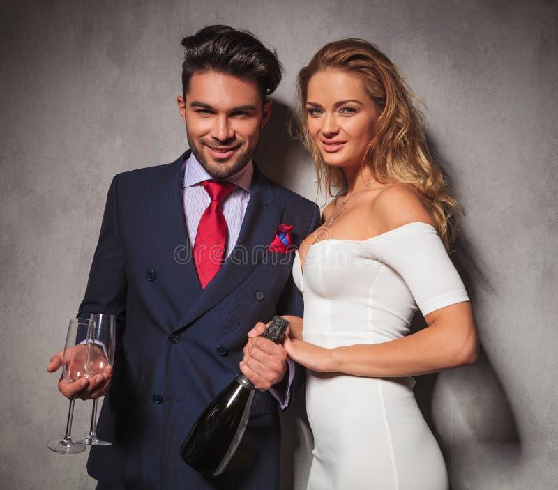 Coppie eleganti felici che tengono una bottiglia di champagne e di vetri fotografie stock