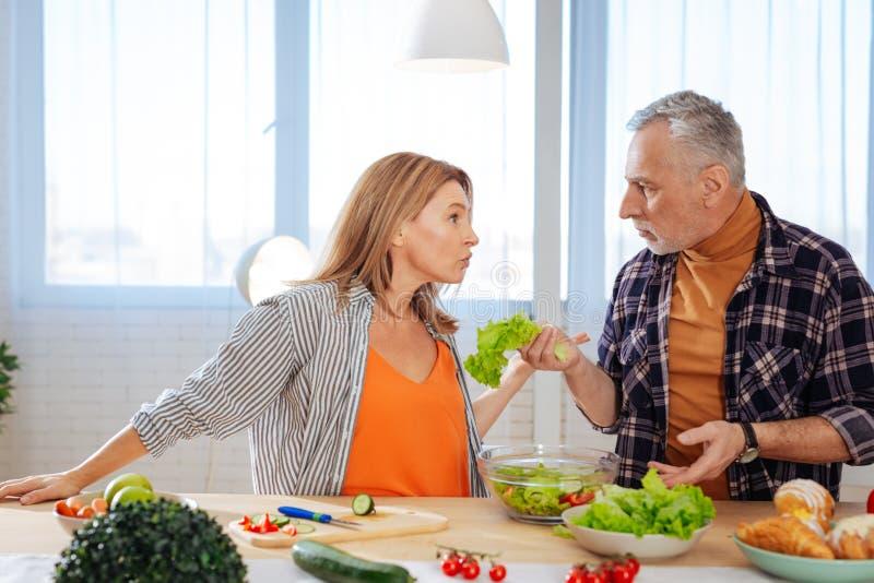 Coppie emozionali che hanno discussione mentre cucinando insalata per pranzo immagini stock