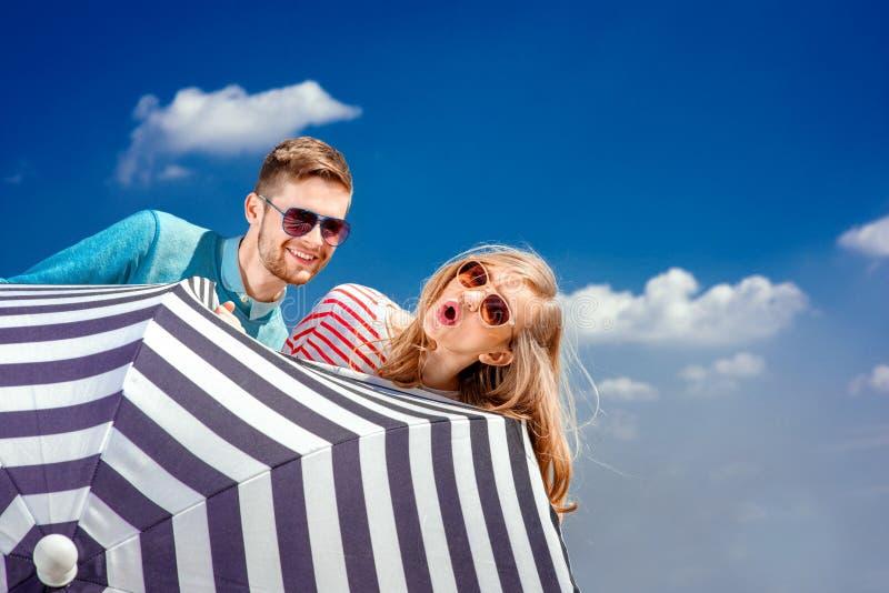 Coppie emozionali che si nascondono dietro l'ombrello e che si divertono sul Th immagine stock