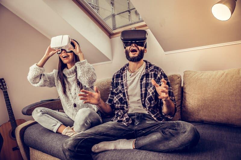 Coppie emozionali piacevoli allegre facendo uso dei vetri di VR immagine stock