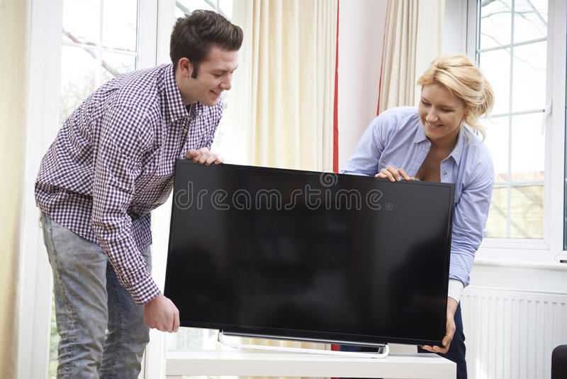 Coppie emozionanti che installano nuova televisione a casa immagine stock