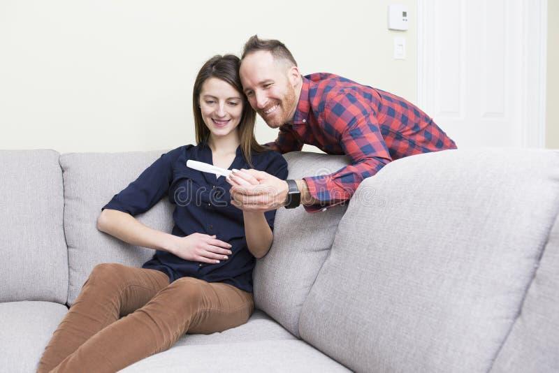 Coppie emozionanti felici che fanno test di gravidanza positivo immagine stock