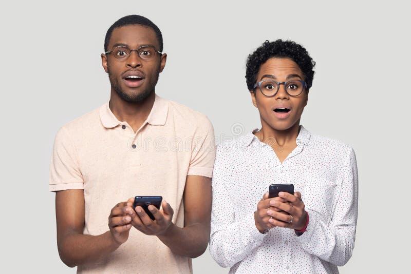 Coppie etniche stupite sorprese dal messaggio sullo smartphone immagine stock