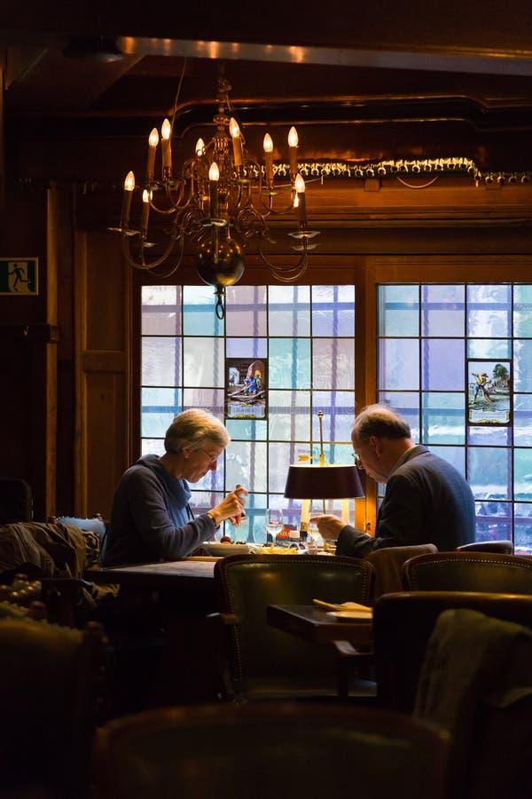 Coppie europee anziane che pranzano ad un ristorante romantico fotografia stock libera da diritti
