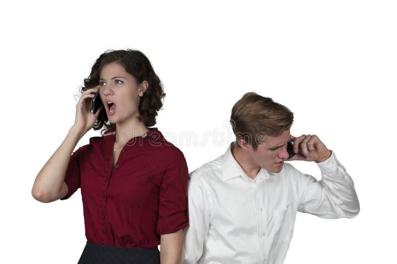 Coppie facendo uso dei telefoni cellulari immagini stock