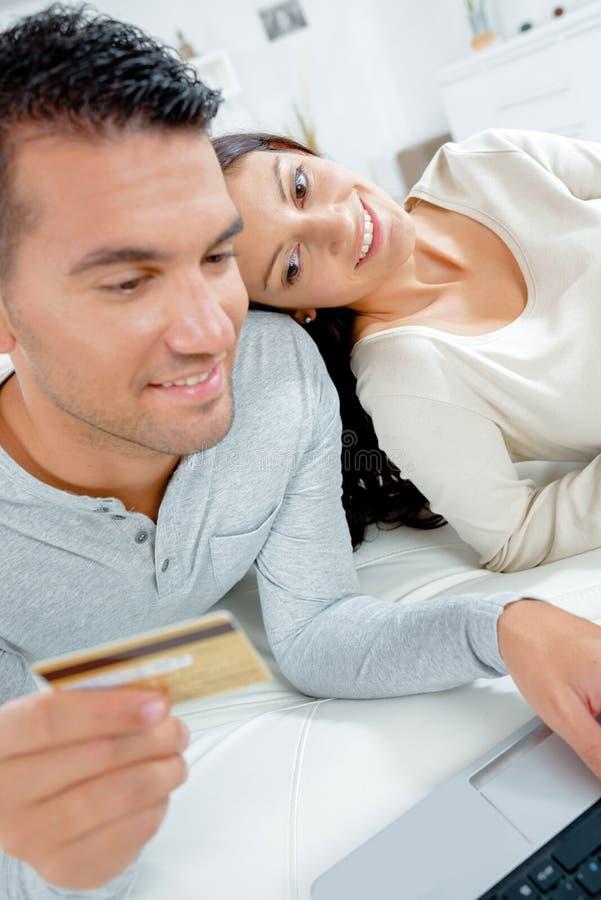 Coppie facendo uso del computer portatile e della tenuta della carta di pagamento fotografia stock libera da diritti
