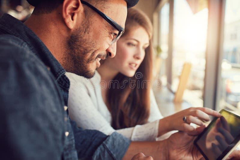 Coppie facendo uso della compressa digitale al caffè fotografia stock libera da diritti
