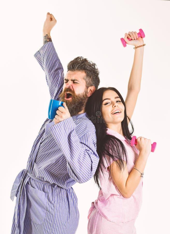 Coppie, famiglia sui fronti sonnolenti, allunganti Le coppie nell'amore in pigiama, accappatoio stanno indietro per appoggiare Ra fotografia stock