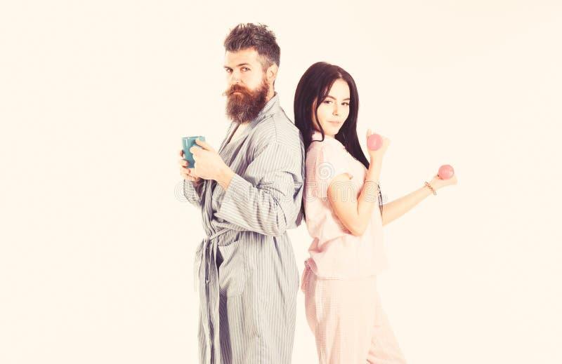 Coppie, famiglia sui fronti sonnolenti, pieni di energia Coppie nell'amore in pigiama, supporto dell'accappatoio isolato su fondo fotografia stock