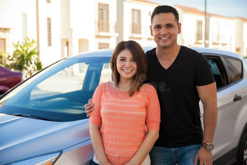 Coppie felici accanto ad un'automobile immagine stock libera da diritti