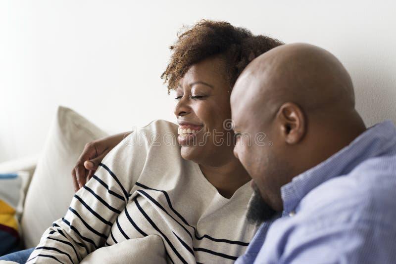 Coppie felici africane che si rilassano a casa fotografia stock
