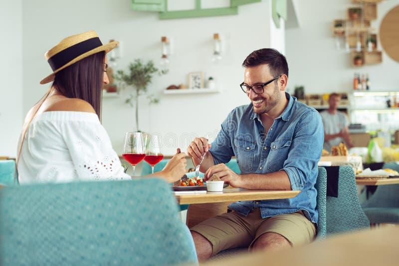 Coppie felici al ristorante che mangia pranzo, divertendosi immagine stock libera da diritti