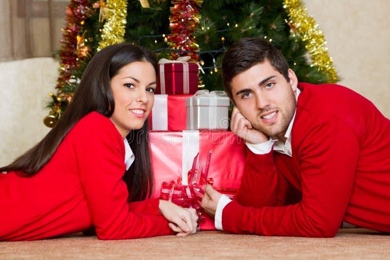 Coppie felici alla notte di Natale che mette su Flor immagini stock