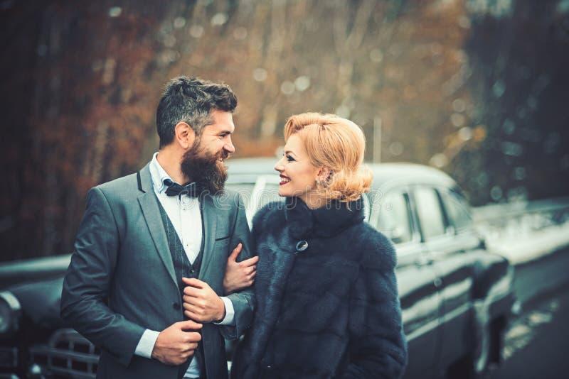 Coppie felici alla retro automobile d'annata nera Amici che vanno sul viaggio di viaggio stradale il giorno di inverno fotografia stock libera da diritti