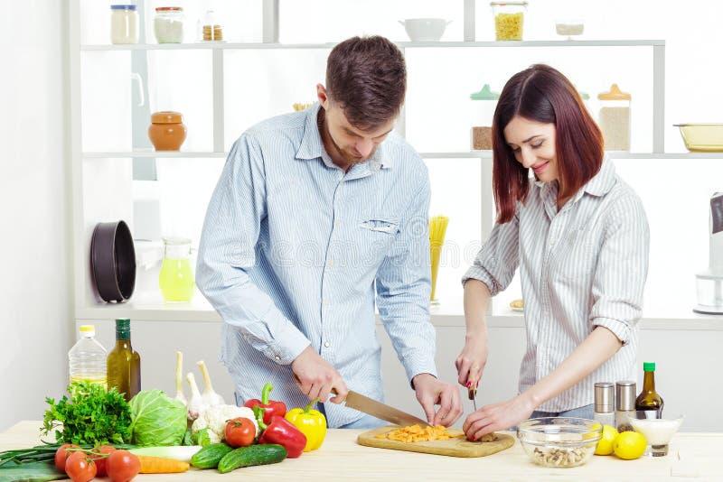 Coppie felici amorose che preparano insalata sana degli ortaggi freschi in cucina immagini stock libere da diritti