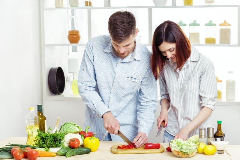 Coppie felici amorose che preparano insalata sana degli ortaggi freschi in cucina fotografia stock