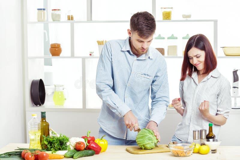 Coppie felici amorose che preparano insalata sana degli ortaggi freschi in cucina fotografia stock libera da diritti