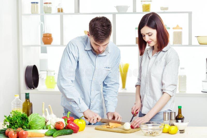 Coppie felici amorose che preparano insalata sana degli ortaggi freschi in cucina fotografie stock libere da diritti