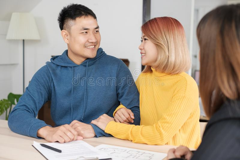 Coppie felici asiatiche che comprano nuova casa con l'agente di agente immobiliare con lo smili fotografie stock