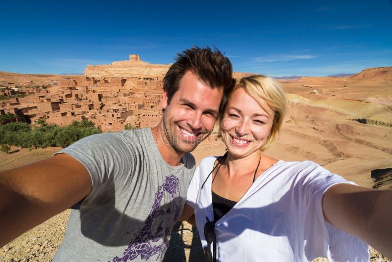 Coppie felici attive che prendono selfie sul viaggio al kasbah di Ait Benhaddou, Ouarzazate, Marocco fotografia stock libera da diritti