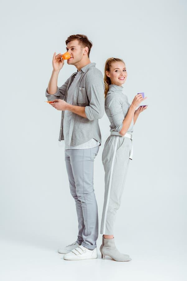 coppie felici in caffè bevente dell'abbigliamento grigio fotografia stock