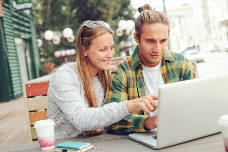 Coppie felici in caffè della via, web che naviga insieme fotografia stock