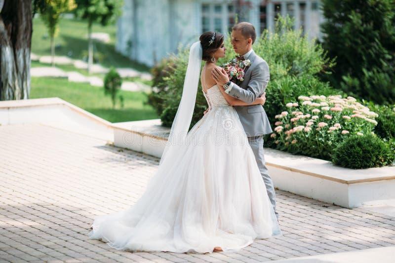 Coppie felici che abbracciano e che vanno in giro nel parco La sposa in un vestito nero con un farfallino e una sposa in un bello immagine stock libera da diritti