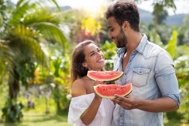 Coppie felici che abbracciano esaminandose fetta dell'anguria della tenuta all'aperto nell'uomo attraente e nella donna del parco immagini stock libere da diritti