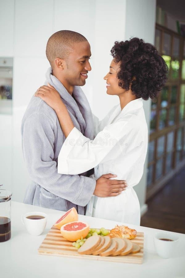 Coppie felici che abbracciano nella cucina fotografie stock