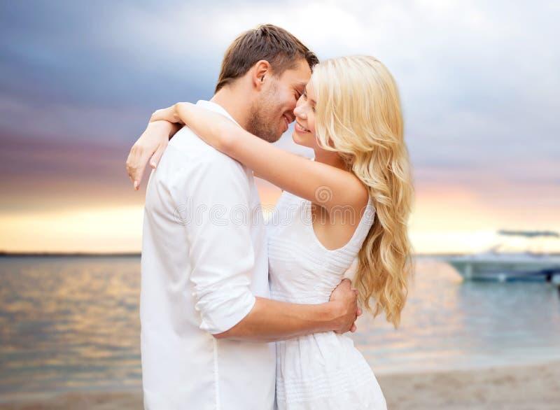 Coppie felici che abbracciano sopra il tramonto alla spiaggia di estate immagini stock