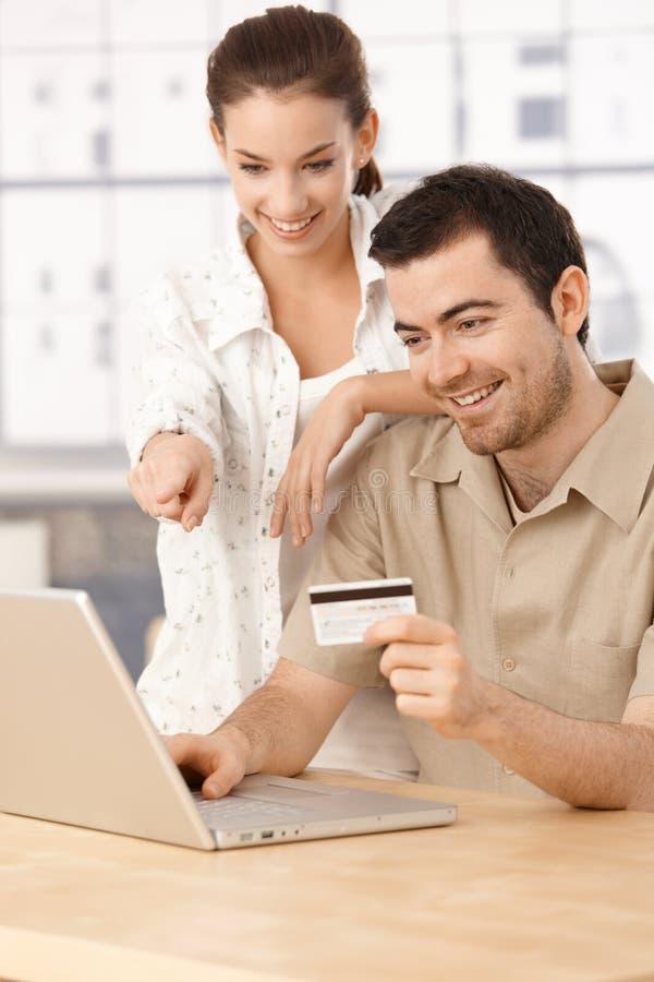 Coppie felici che acquistano in linea avendo sorridere di divertimento fotografie stock libere da diritti