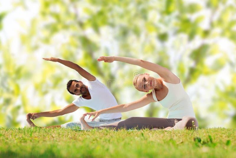 Coppie felici che allungano e che fanno gli esercizi di yoga immagine stock