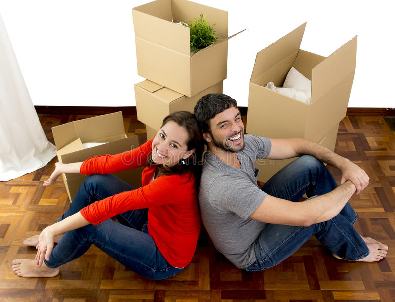 Coppie felici che avvicinano in una nuova casa che disimballa le scatole di cartone fotografie stock libere da diritti