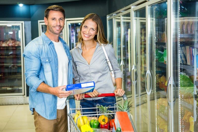 Coppie felici che comprano alimento congelato immagini stock libere da diritti