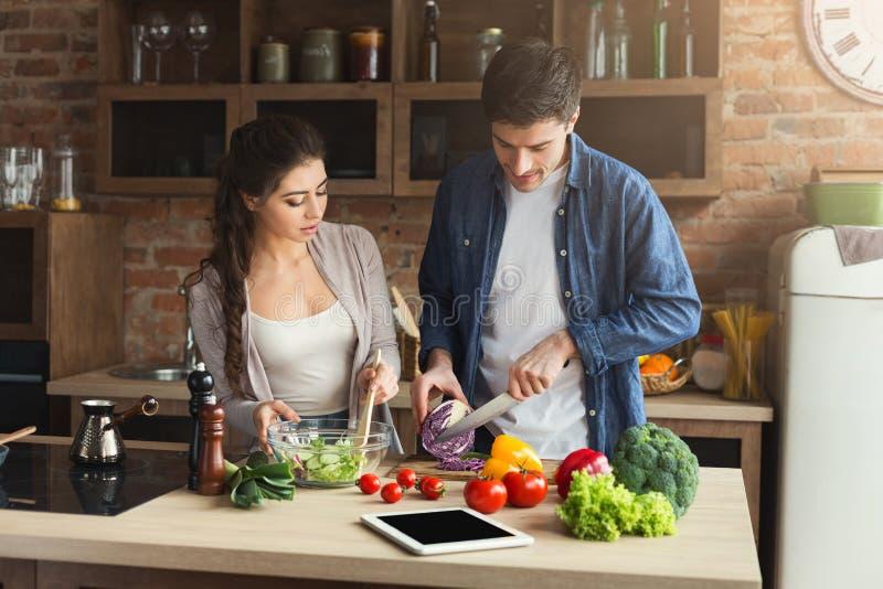 Coppie felici che cucinano insieme alimento sano immagine stock