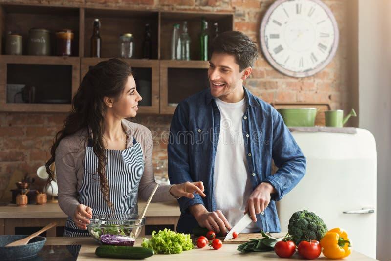 Coppie felici che cucinano insieme cena sana fotografia stock libera da diritti