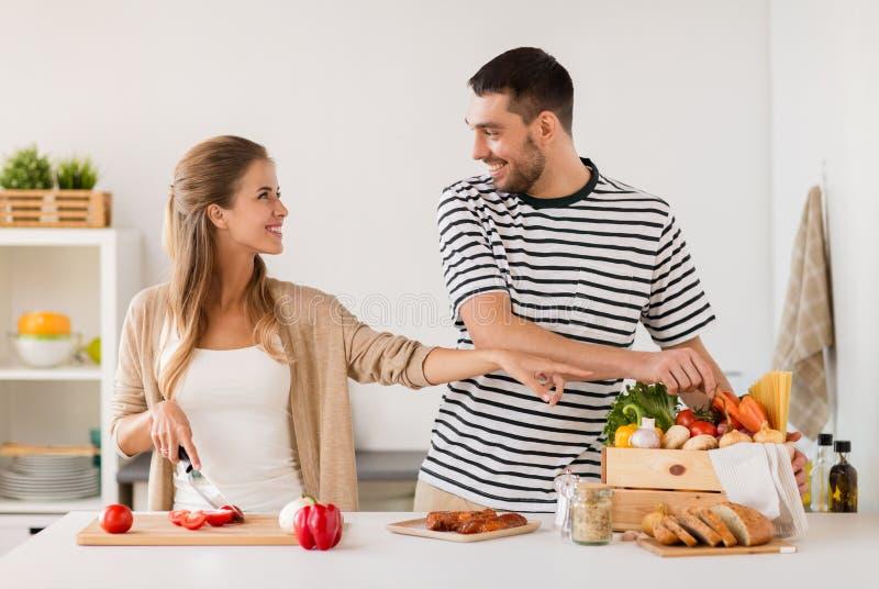 Coppie felici che cucinano la cucina dell'alimento a casa immagini stock libere da diritti