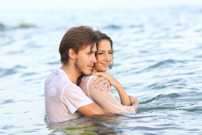 Coppie felici che distolgono lo sguardo bagnanti sulla spiaggia fotografia stock