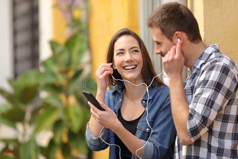 Coppie felici che dividono musica in una via variopinta fotografia stock