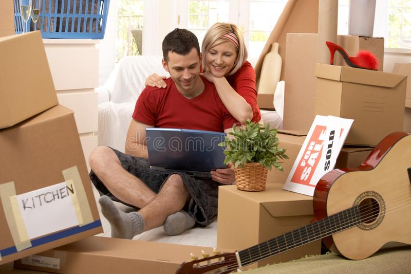 Coppie felici che esaminano calcolatore in nuova casa fotografia stock libera da diritti