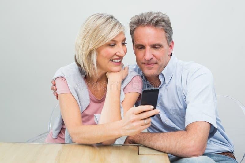 Coppie felici che esaminano telefono cellulare fotografia stock libera da diritti