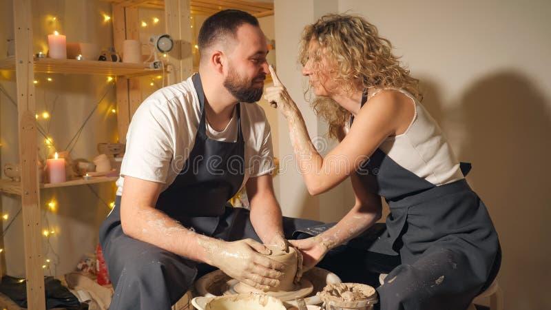 Coppie felici che fanno la brocca dell'argilla sul tornio da vasaio fotografia stock libera da diritti