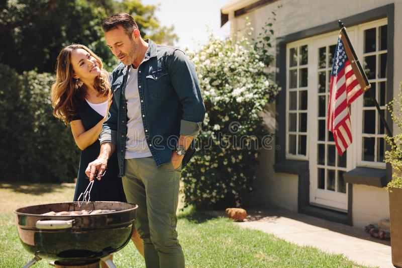 Coppie felici che fanno un barbecue nel loro cortile fotografie stock