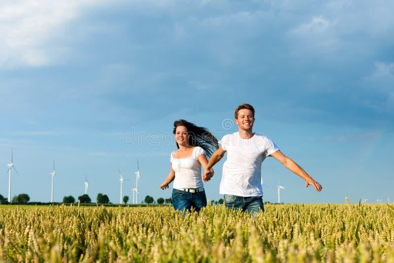 Coppie felici che funzionano sopra il grainfield immagini stock libere da diritti