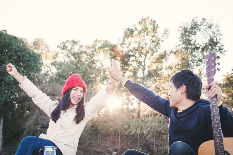 Coppie felici che giocano chitarra nella stagione invernale della natura immagine stock libera da diritti
