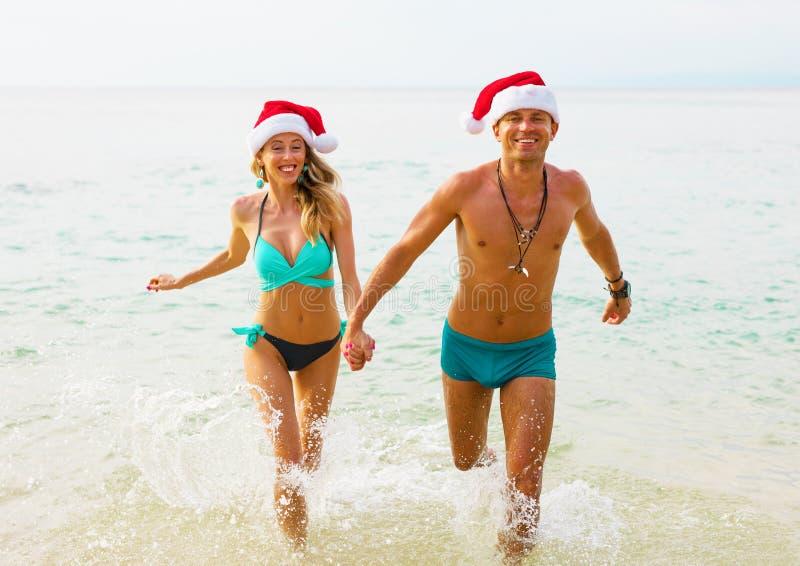 Coppie felici che godono delle vacanze invernali sulla spiaggia fotografie stock libere da diritti